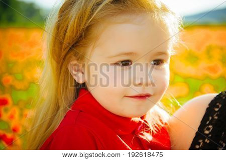 smiling little boy or child with long blonde hair in red shirt on hand of mother in flower field of poppy summer spring childhood and happiness ecology and environment mothers day and family