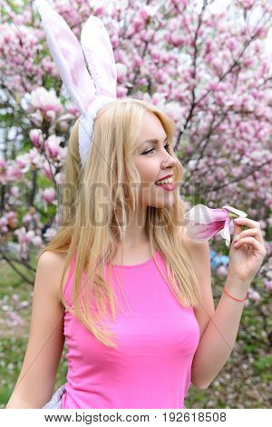 woman or cute girl happy with magnolia flower with pink bunny ears on long blond hair in rosy top in blossoming garden on floral environment. Spring. Easter holidays celebration