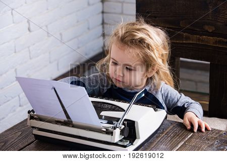 boy or small kid with typewriter and paper working at table