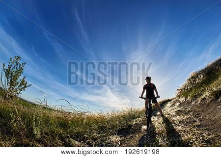 Wide angle of the cyclist with mountain bicyclist against beautiful landscape. Young sportsman dressed in the black sportwear and sporty shoes, with backpack and helmet. Blue sky with sunrise. Concept of the healthy and active lifestyle.
