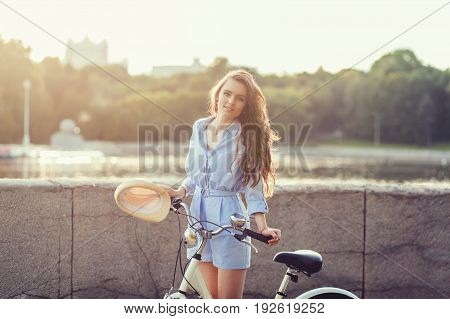 Cheerful woman in hat near bicycle in sunset