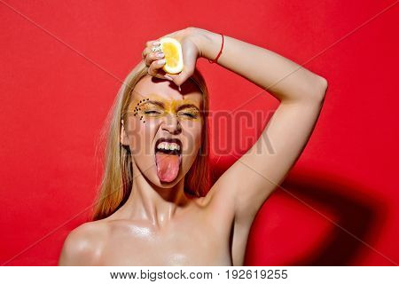 Young Girl Squeeze Yellow Lemon On Red Background