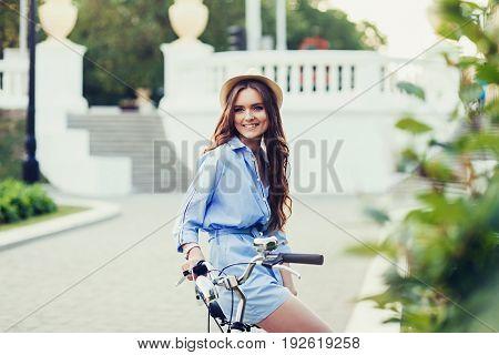 Beautiful woman in hat smiling sitting on bike
