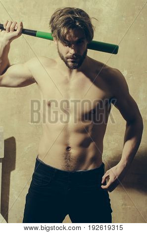 Athletic man. handsome athlete or sexy macho with naked muscular torso six pack ab in jeans standing with green baseball bat in strong hands bicepstriceps on beige wall. Sport training fitness