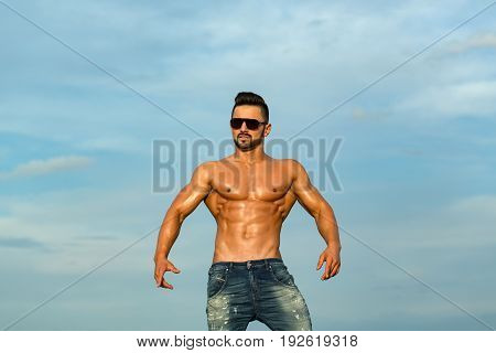 Sexy Man With Muscular Body In Sunglasses On Blue Sky