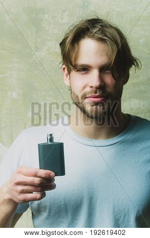 Macho Man Posing With Black Perfume Bottle