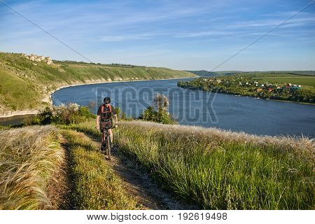 Young cyclist riding mountain bike uphill along a country road above river. Sportsman dressed in the black sportwear and sporty shoes, with backpack and helmet. Extreme travel in the countryside. Concept of the healthy lifestyle.
