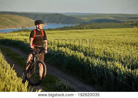 Attractive cyclist stands on the bike on the trail of the hay field in summer season. Young sportsman dressed in the black sportwear, with helmet and backpack. Extreme travel in the countryside. Concept of the healthy and active lifestyle.