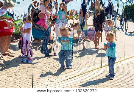 Samara Russia - May 12 2017: Little girl near the giant stainless steel mirror at the city park in summer sunny day