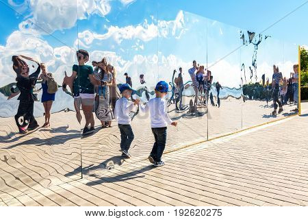 Samara Russia - May 12 2017: Little boy near the giant stainless steel mirror at the city park in summer sunny day