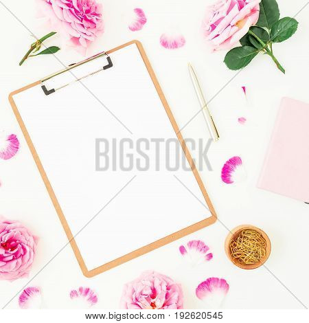 Blogger of freelancer beauty composition. Workspace with clipboard, notebook, pen and pink roses on white background. Flat lay, top view.