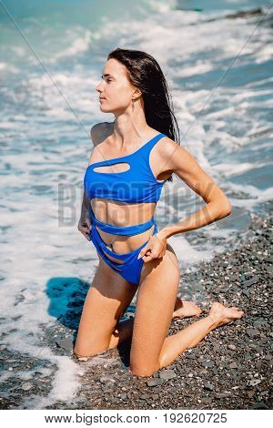 Brunette slim woman with perfect body posing on beach, wearing stylish blue bikini and ocean