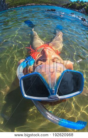 Fisheye view of young woman in crystal waters. Female snorkeling in orange bikini sunbathing in tropical sea. Vast angle view of snorkeler lifestyle relaxing. Leisure, holidays, water sports concept.