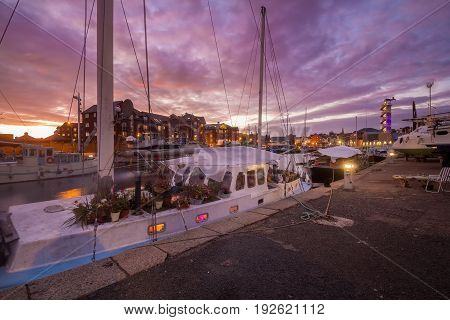 Yacht in the harbor. On board the yacht there are a lot of pots with flowers. Inside the light is on. Beautiful sunset. Exeter. Devon. England