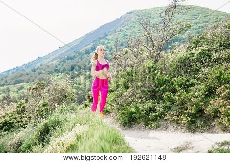 Fitness perfect woman running in outdoors. Sporty slim girl in mountains.