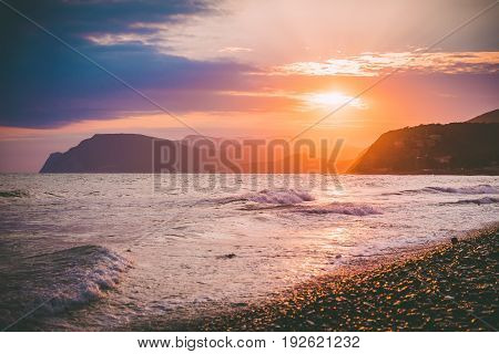 Sunset or sunrise on ocean and mountains in the distance. Stones beach and waves in sea