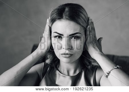 Happy woman covering her ears with hands. The girl expresses various emotions. Black and white photo