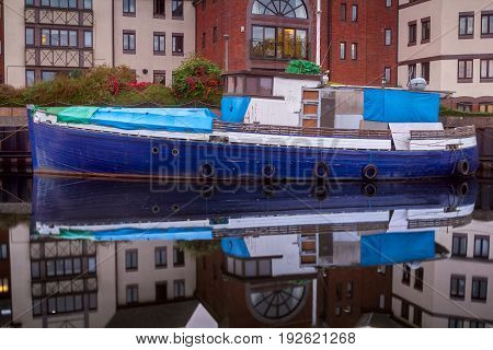 The old ship is moored on a narrow canal. Next to the apartment buildings. Quiet water without waves. The ship is reflected in the smooth surface of the water. Exeter. Devon. England