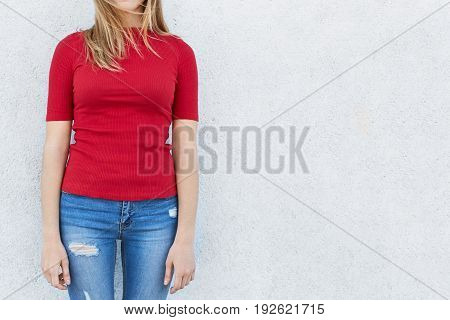 Unrecognizable Female Model Wearing Red Sweater And Jeans Posing Against White Concrete Wall. Croppe