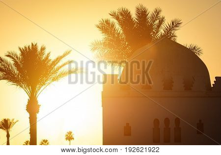 Beautiful sunset moment with Islamic church palms at background. Silhouette of palm trees with old religious building in Marrakesh town with gold sun rays and lens flare. Wanderlust travel concept.