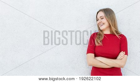 Cheerful Female With Fair Hair Wearing Red Dress Standing Crossed Hands Posing Against White Wall Wi