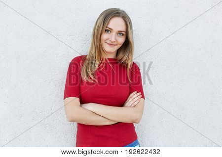Confident Woman In Red Clothes Having Blue Eyes, Fair Hair And Freckles On Her Face Looking Into Cam