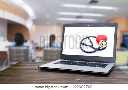 Laptop notebook computer with red heart and stethoscope on white background on wooden table with blurred hospital background heart health care and medical technology concept selective focus