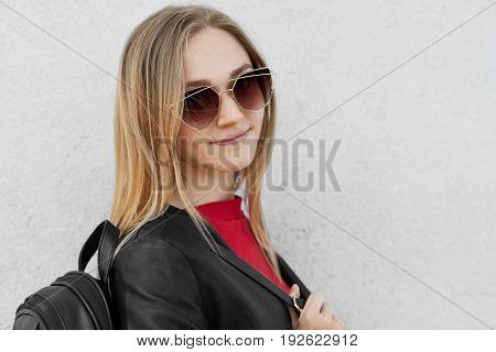 Sideways Portrait Of Stylish Teenage Girl With Fair Hair Wearing Big Trendy Sunglasses, Leather Jack