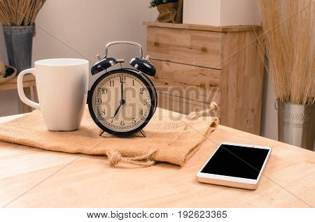 white coffee cup smartphone and black retro alarm clock times at 7 o'clock morning on wooden table selective focus copy space vintage color tone