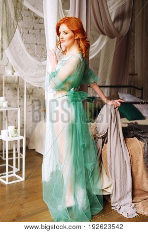 Tender redhead woman in transparent green peignoir and white lingerie on the floor near her bed in bedroom waiting for a man