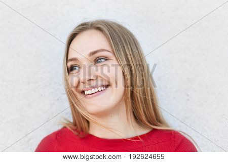 Charming Female Model With Straight Fair Hair Looking With Her Blue Eyes Aside Having Broad Smile De