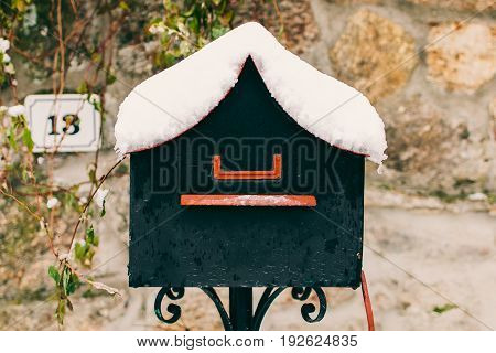 Vintage mailbox covered with snow. Post box background. Letterbox in vintage style. Old grey mailbox in stone background.