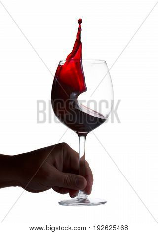 Hnad holding wine glass with splashing red wine isolated on white background, wine tasting concept