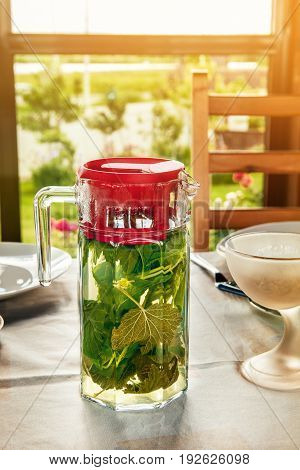 Cooling vitamin detox drink made from crushed mint leaves and currants in a large transparent glass jar with red lid is on the table.