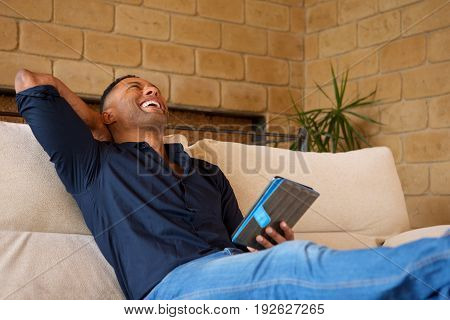 Portrait of laughing young african american man looking away with digital tablet at home