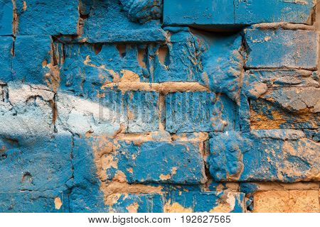 Old brick wall made of clay brick with cracks. Painted in blue and yellow