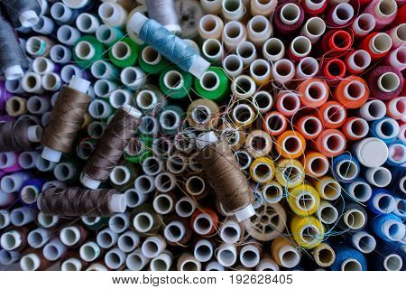 A lot of colorful thread spools used in textile industry. Top view