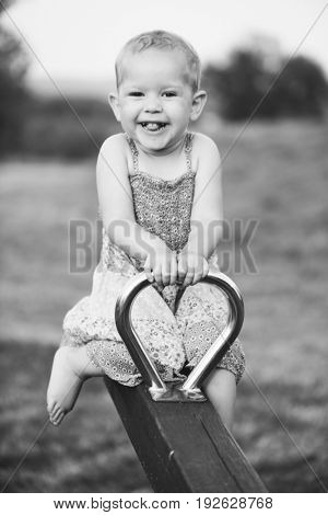 Happy little girl is swinging on see-saw outdoor. Teeter totter riding by a cute smiling kid.