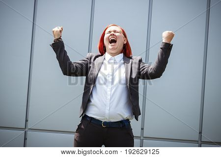 Success! Victory! Happy Successful Red-haired Girl Boss, Businesswoman In A Suit Emotionally Celebra