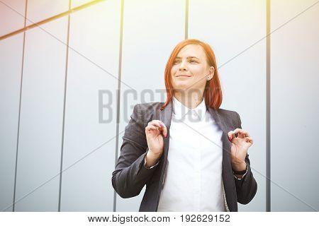 Satisfied Successful Red-haired Girl Boss, Businesswoman In A Suit, With Space For Text And Advertis