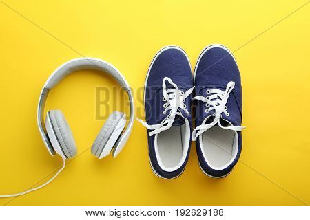 Blue Sport Shoes With Headphones On Yellow Background