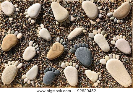Pebble stones arranged like footprints on the beach. Family summer vacation concept