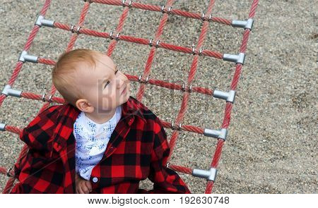 cute little baby in a red checkered shirt on a swing