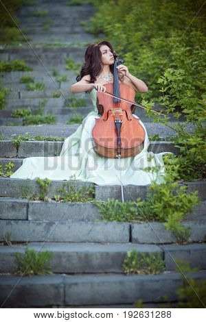 Woman in a green dress with a cello on an old staircase in the street