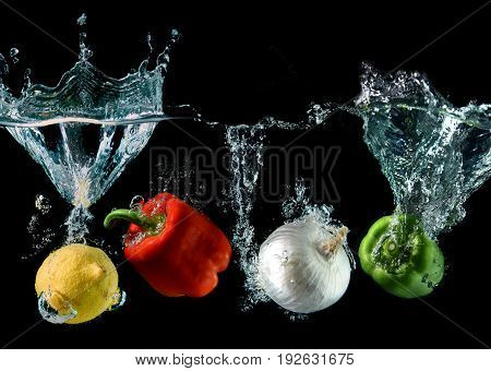 Splash Water With Droping Bell Pepper ,lemon And Onion
