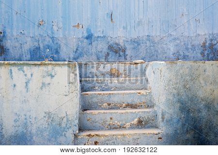 blue abandoned grunge cracked stucco wall and stairs