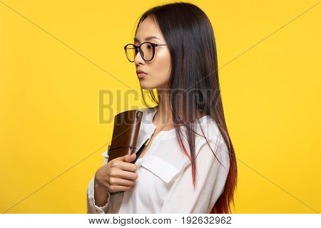 Woman with glasses, woman with a notepad, woman on a yellow background.