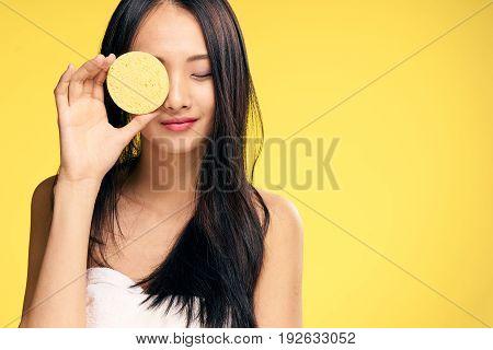 Skin care, woman with sponge, sponge, woman on yellow background portrait.