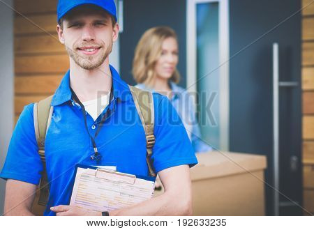 Smiling delivery man in blue uniform delivering parcel box to recipient - courier service concept