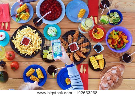 Top view of group of people having dinner together while sitting at wooden table. Food on the table. People eat fast food. Photograph food
